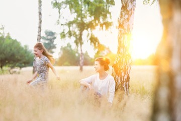 Loving mother watches her daughter play in the woods with yellow lens flare in background