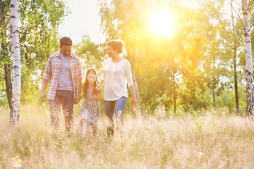 Happy family walking in wheat field with yellow lens flare in background
