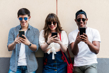Multiracial stylish friends with smartphones on street