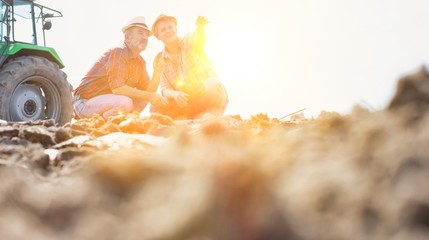 Farmers examining soil in field with yellow lens flare in background