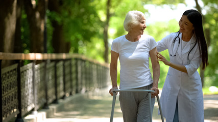 Fototapeta Female doctor helping elderly woman with walking frame, hospital park, outdoors obraz