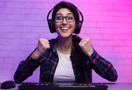 Excited woman celebrating victory in online game