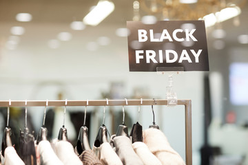 Background image of BLACK FRIDAY sigh in window display above rack with clothes on sale in shopping mall, copy space
