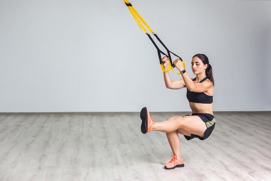 Portrait of young athletic woman in sportswear doing squat exercise, training legs and glutes muscular with fitness straps in the gym. Functional training. Isolated, trx concept, white wall background