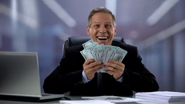Cheerful manager holding dollar banknotes, rejoicing successful profitable deal