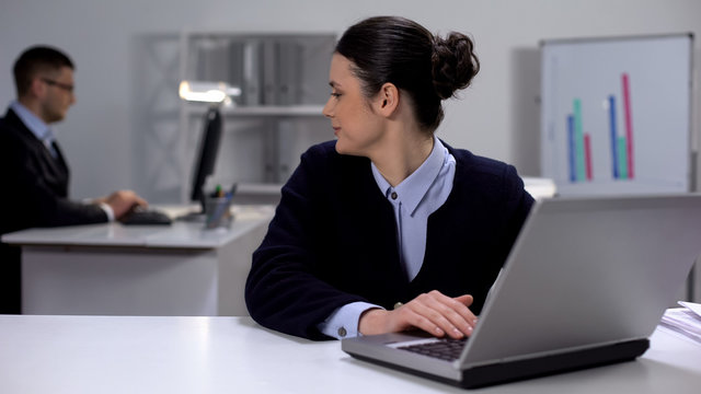 Cute female manager working on laptop, looking at male colleague, secret love