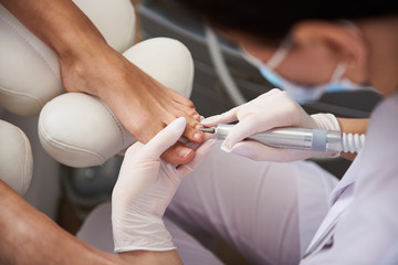 Foto op Plexiglas Pedicure Pedicurist using electric nail drill while doing pedicure for young lady