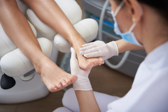 Pedicurist gently massaging woman leg after pedicure
