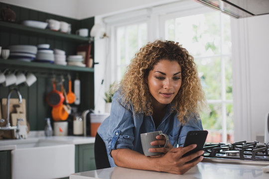 Adult female looking at smartphone whilst having morning coffee
