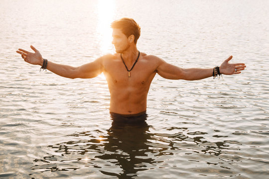 Man with perfect muscular stands in the water at sunset flinging his hands to the side. Concept of freedom relaxation. Place for text or advertising
