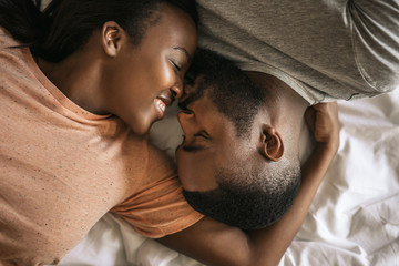 Loving young African American couple lying in bed together