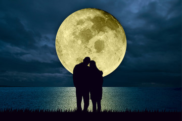 Silhouette of couple embracing standing at the beach at night watching the moonlight from a big full moon shining in the ocean. Love and romance concept. Moon image furnished by NASA.