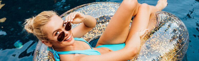 panoramic shot of smiling sexy young woman in swimsuit and sunglasses lying on swim ring in pool
