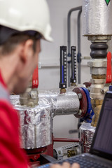 Energy industry. A technician dressed in red overalls and a white helmet checking the heating parameters. Heating water distribution technology. Service work in the power industry. Heating season.