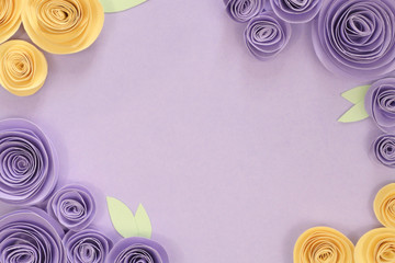 Pastel violet and yellow paper craft rose flower flat lay background with flowers and leaves on around the border and empty copy space in middle