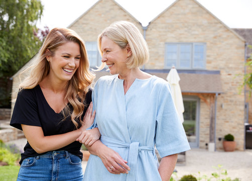 Senior Mother And Adult Daughter Walking And Talking In Garden Together