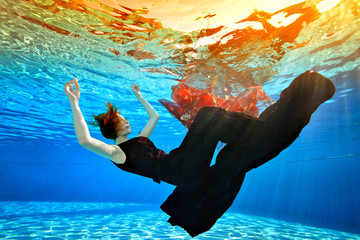 A young girl sinks to the bottom of the pool, arms outstretched, in a fashionable burgundy dress, with red hair, against the background of sunlight. Surreal underwater picture. Concept.