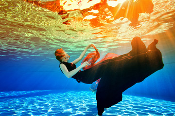 Surreal underwater picture. A young girl sinks back to the bottom of the pool in a Burgundy dress, with red hair, against the sunlight from the surface. Concept.