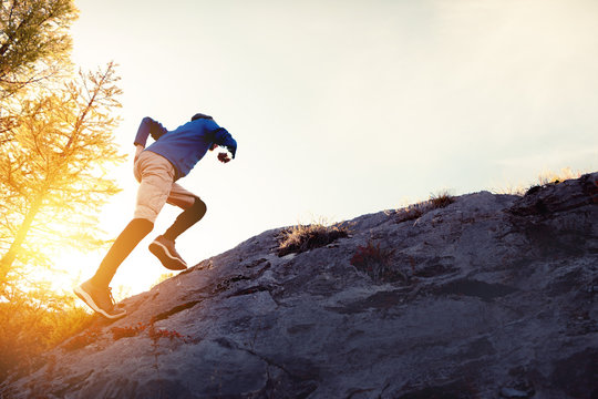 Man runs uphill on big rock at sunset