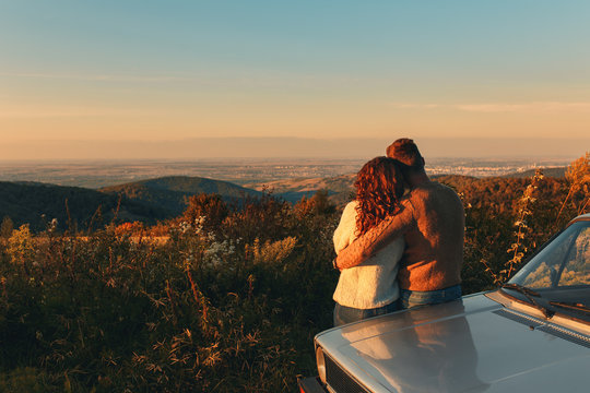 Rear view of beautiful young couple resting after road trip leaning against car and enjoying the view.