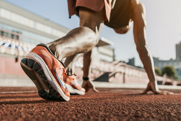 Close up of male athlete getting ready to start running on track . Focus on sneakers
