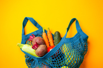 Vegetables in mesh cotton bag on yellow background