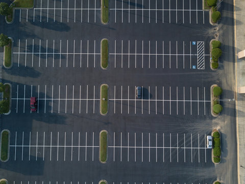 Looking down on a large, mostly empty parking lot.