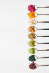 Various types of colorful superfood powders on white table
