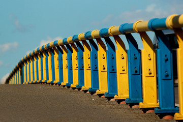 Metal railing on a bridge in Kyiv, Ukraine. Painted in yellow and blue colors of Ukrainian flag.