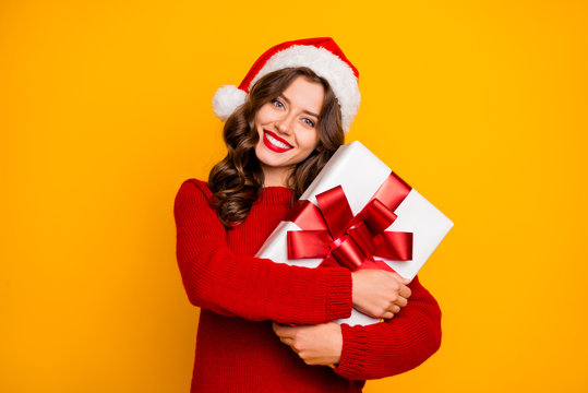 Pretty overjoyed lady holding large giftbox close to chest wear knitted jumper and santa hat isolated yellow background