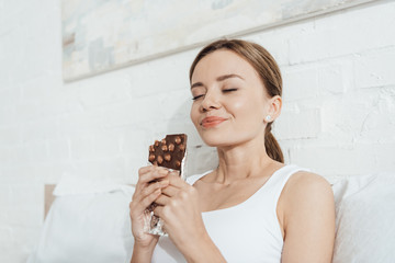 low angle view of smiling young woman eating chocolate with nuts with closed eyes in bed