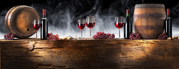 Bottles with red wine on the smoke background