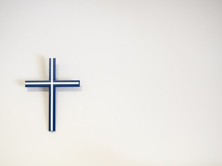 Blue and white catholic cross on a wall with copy space