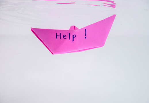 Close-up of sinking folded paper boat into the water. Mental state and Emotional concept.