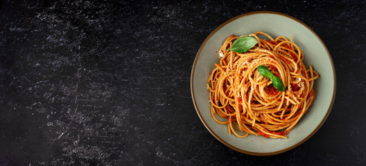 Spaghetti with tomato sauce on black background