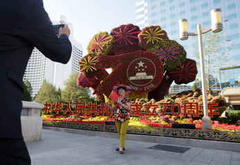 Woman poses for a photo next to an installation facing the Chang'an Avenue in Beijing