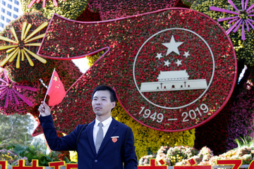 Man poses for a photo next to an installation facing the Chang'an Avenue in Beijing