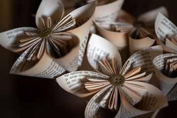Stylish origami-type hand-made folded paper flowers constructed from buttons and pages from an old book