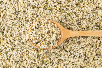 Hemp seeds background with wooden spoon