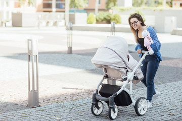 Mother walking with hewborn baby in stroller, woman holding soft toy and spend time funny.