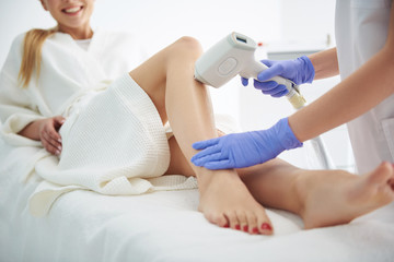 Young woman in white bathrobe receiving laser epilation in modern beauty salon