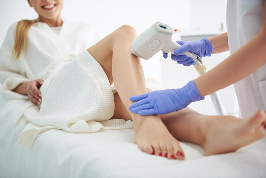 Young woman in white bathrobe receiving laser epilation in modern beauty salon