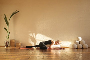 In de dag School de yoga Woman practiving restorative yoga in a beautiful studio