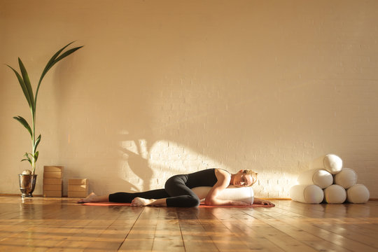 Woman practiving restorative yoga in a beautiful studio