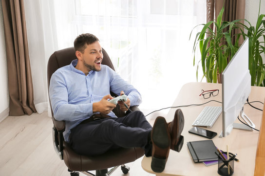 Carefree man playing video games in office