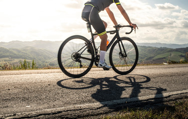Cyclist sports on road. Sun Rays and shadows from the bike on the road.