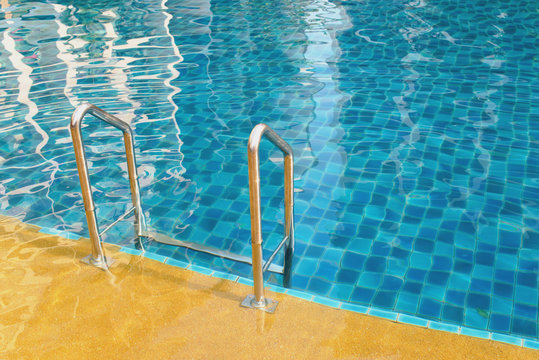 Swimming pool with grab bars ladder and stairs.