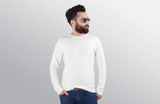 Closeup of standing male model wearing white plain crew neck long sleeve shirt in blue denim jeans pant. Isolated background