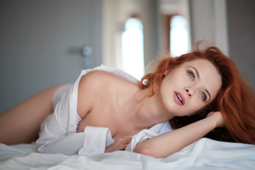 very sensual woman in sexy pose on bed with long natural redhair, open shirt and white panties
