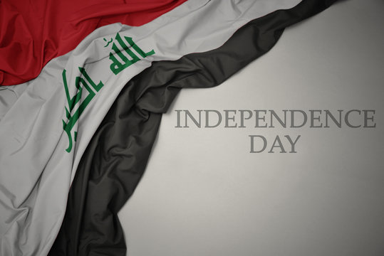 waving colorful national flag of iraq on a gray background with text independence day.